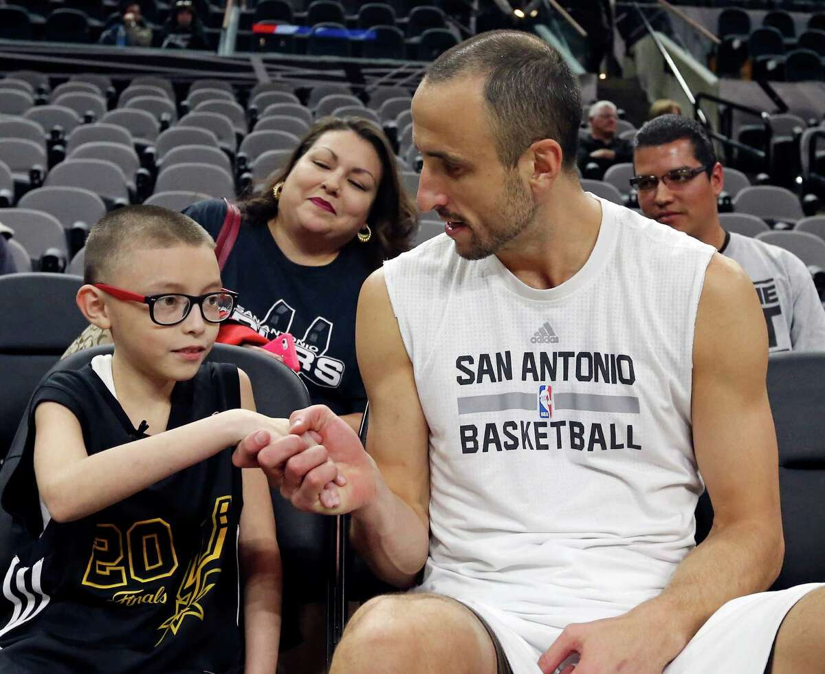 Ginobili San Miguel-Ramirez, 10, (left) talks with San Antonio Spurs' Manu Ginobili before the Spurs and Utah Jazz game as his mother Renee San Miguel-Ramirez, 36, (rear from left) and father Jorge Ramirez, 38, look on Monday Dec. 14, 2015 at the AT&T Center.