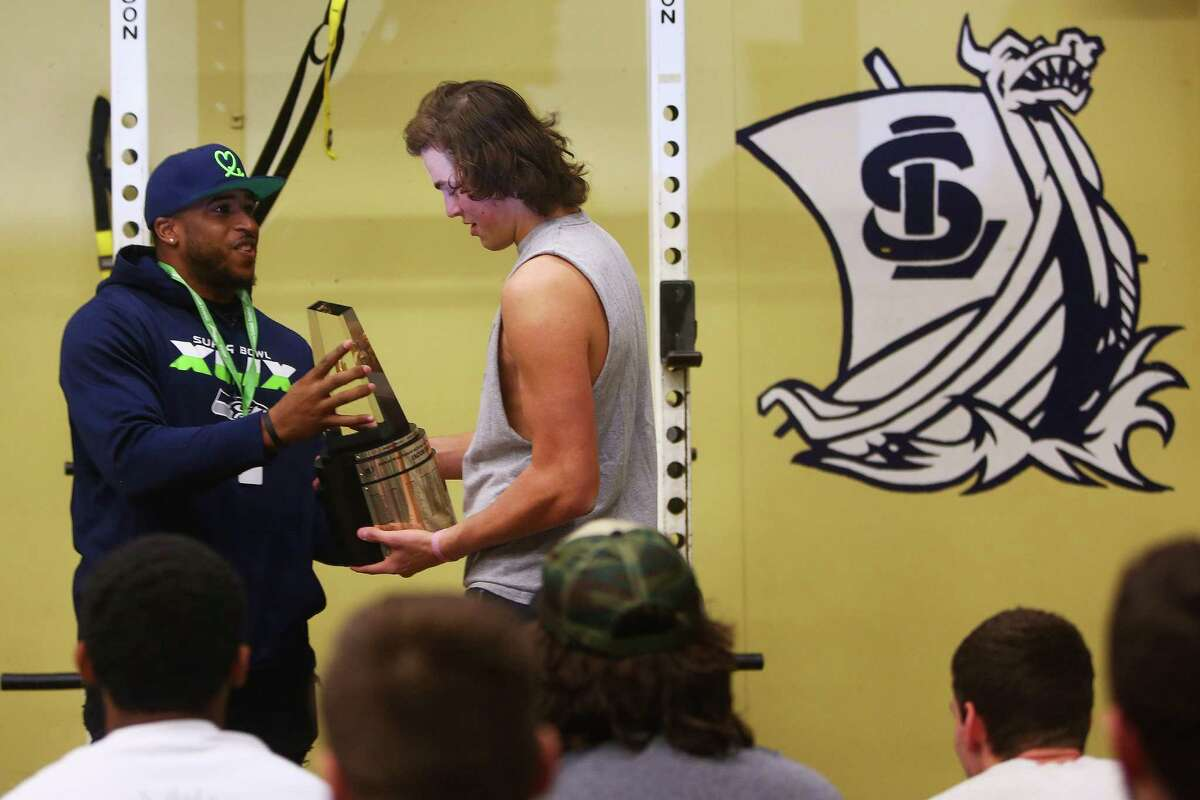 Seahawks linebacker Bobby Wagner (left) presents the Gatorade National Football Player of the Year award to Lake Stevens High School quarterback Jacob Eason during a surprise ceremony at the school, Tuesday morning, Dec. 15, 2015. Eason also announced at the ceremony he will be sticking by his verbal commitment to play for the University of Georgia next season.