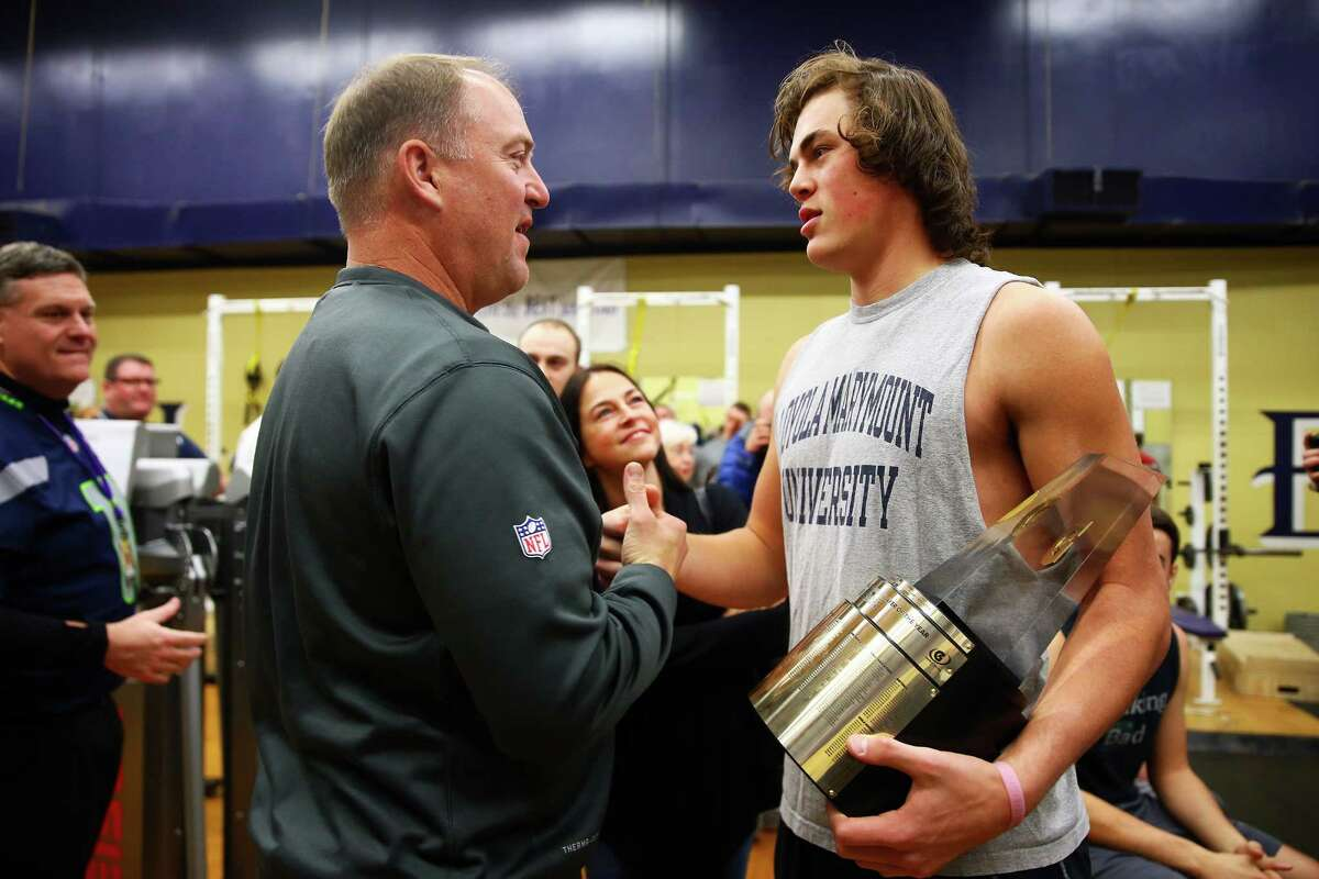 Tony Eason (left) congratulates his son Jacob after Jacob was presented with the Gatorade National Football Player of the Year award by Seahawks' Bobby Wagner during a surprise ceremony at Lake Stevens High School, Tuesday morning, Dec. 15, 2015.