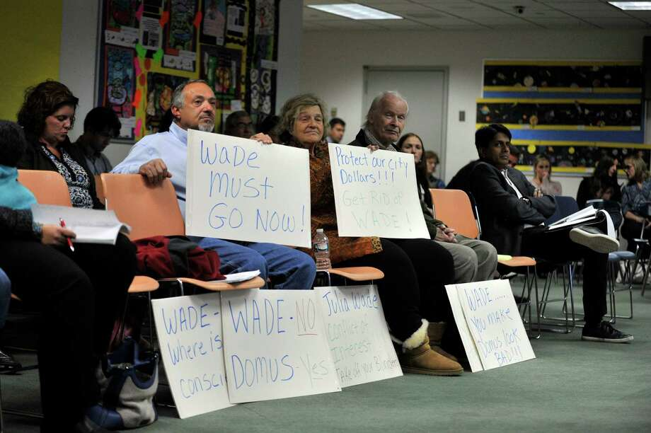 Community members attended an October Board of Education meeting with signs calling for the resignation of board member Julia Wade. Photo: Michael Cummo / Hearst Connecticut Media / Stamford Advocate