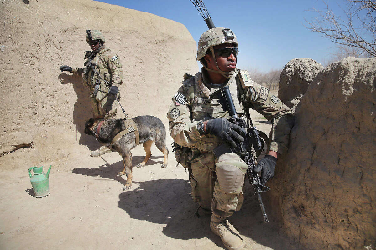 KANDAHAR, AFGHANISTAN - MARCH 01: PFC Misiri Parker from Zion, Illinois with the U.S. Army's 4th squadron 2d Cavalry Regiment keeps watch while SRA Brandon Hinton (L) from Oklahoma City, Oklahoma conducts a search with his dog Dan during a joint patrol through a village with soldiers from the Afghan National Army (ANA) on March 1, 2014 near Kandahar, Afghanistan. President Obama recently ordered the Pentagon to begin contingency planning for a pullout from Afghanistan by the end of 2014 if Afghanistan President Hamid Karzai or his successor refuses to sign the Bilateral Security Agreement.