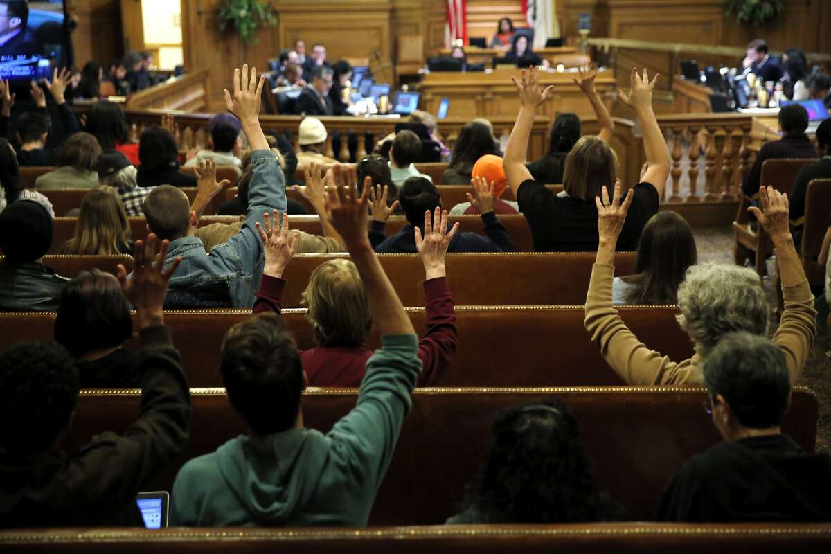 Audience members wave their fingers to applaud the comments of a supervisor during a Board of Supervisors meeting at City Hall in San Francisco, California, on Tuesday, Dec. 15, 2015.