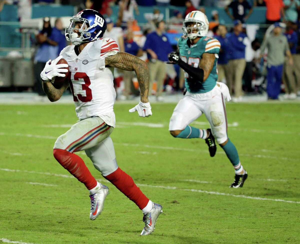 New York Giants wide receiver Odell Beckham (13) runs for a touchdown during the second half of an NFL football gam against the Miami Dolphins, Monday, Dec. 14, 2015, in Miami Gardens, Fla. (AP Photo/Wilfredo Lee) ORG XMIT: SLS120