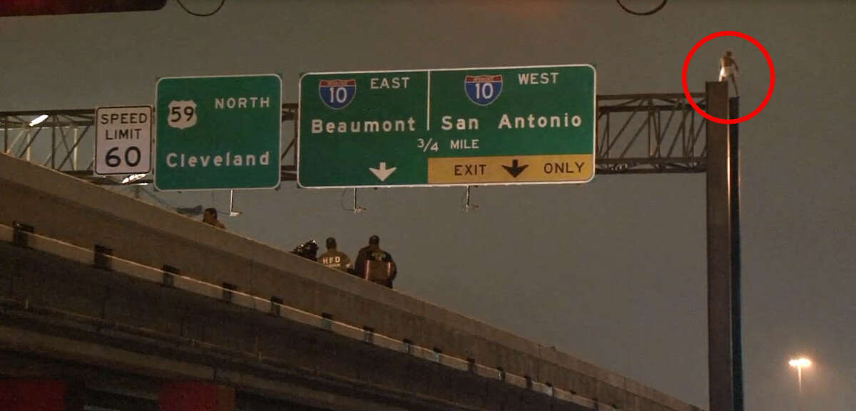 A man wearing nothing but a pair of white underwear scaled a sign over Highway 59 near George R. Brown Convention Center in downtown Houston on Tuesday night, Dec. 15, 2015, holding up traffic in both directions until Houston Police could talk him down.