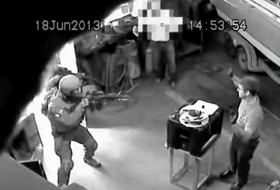 Frame grab from FBI surveillance video showing FBI agents raiding a garage where Glendon Scott Crawford, right, worked on a homemade radiation device he built with the intent to massacre Muslims. (FBI)