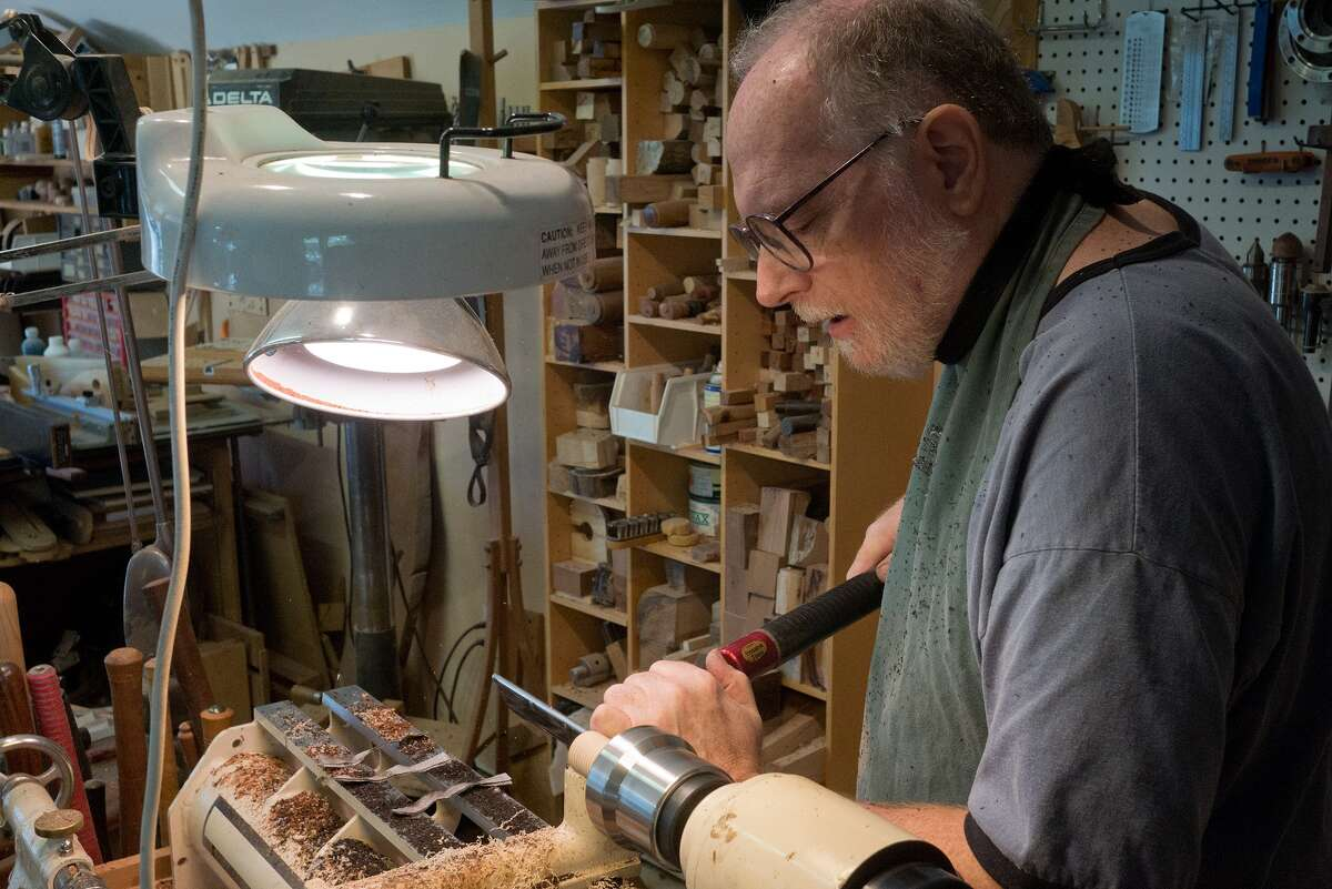 Woodworker Tom Irven is busy in his Bellaire studio. Irven says he uses a lathe to create woodturnings with a sense of movement and playfulness.