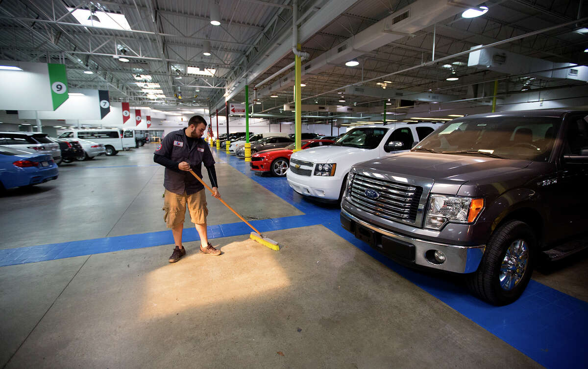 """Jorge Zelaya sweeps the floor of a Texas Direct Auto facility, Tuesday, Dec. 15, 2015, in Meadows Place, Texas. Vroom, an online retailer of used cars, has agreed to acquire Texas Direct Autos, the locally based """"pioneer"""" in online car retailing. Everything is done online -- buying, financing and selling."""