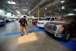 "Jorge Zelaya sweeps the floor of a Texas Direct Auto facility, Tuesday, Dec. 15, 2015, in Meadows Place, Texas. Vroom, an online retailer of used cars, has agreed to acquire Texas Direct Autos, the locally based ""pioneer"" in online car retailing. Everything is done online -- buying, financing and selling."
