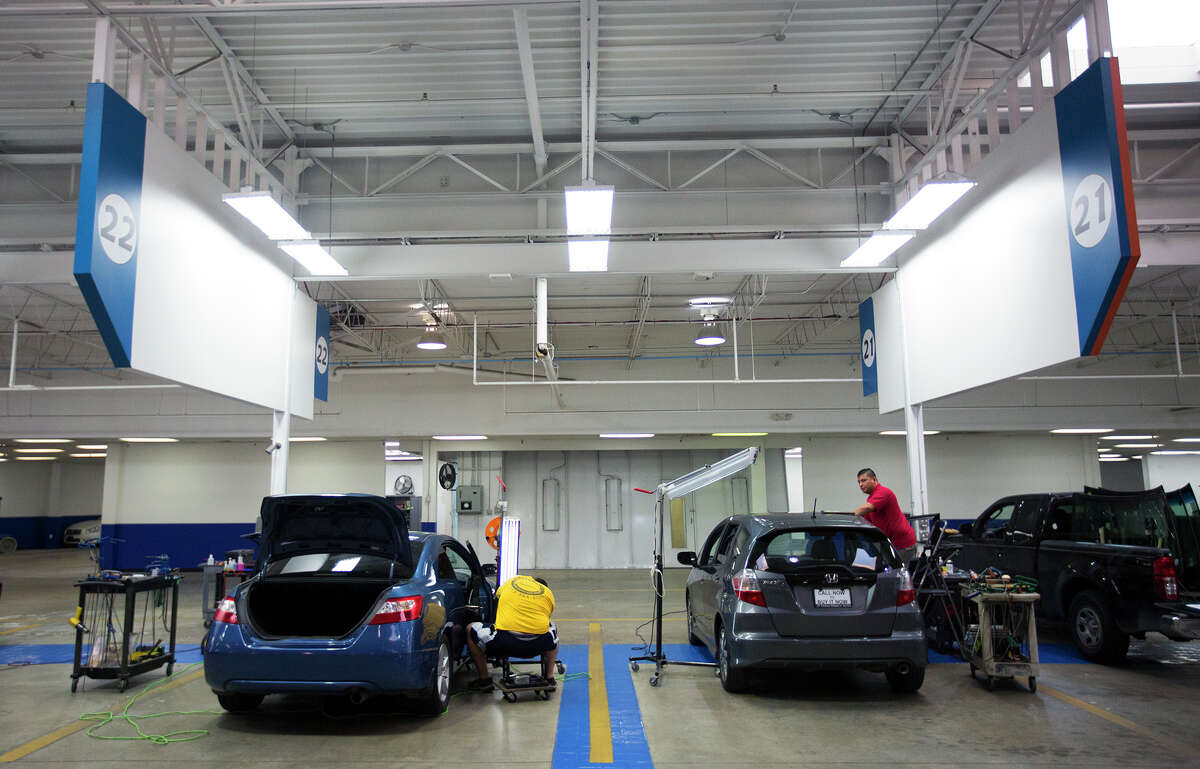 """Workers prepare cars for resell at a Texas Direct Auto facility, Tuesday, Dec. 15, 2015, in Meadows Place, Texas. Vroom, an online retailer of used cars, has agreed to acquire Texas Direct Autos, the locally based """"pioneer"""" in online car retailing. Everything is done online -- buying, financing and selling."""