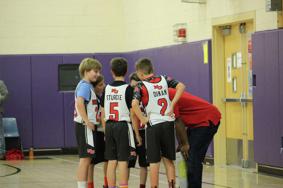 The New Canaan red 5's huddle during a timeout. Photo: Contributed / New Canaan News