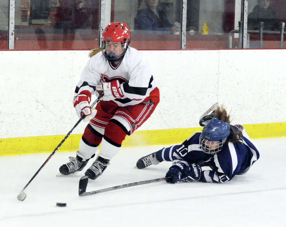 Riley Ellsworth of Greenwich High School, left, goes for the puck as Darien's Corinne Bevill (#10), right, dives for the stick check during the girls high school ice hockey game between Greenwich High School and Darien High School at Hamill Rink in Greenwich, Conn., Tuesday night, Dec. 15, 2015. Photo: Bob Luckey Jr. / Hearst Connecticut Media / Greenwich Time