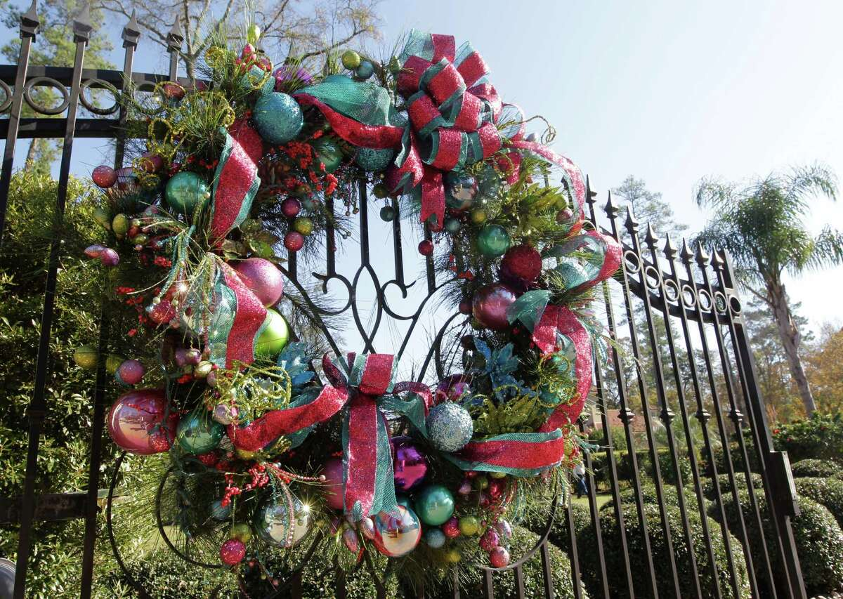 A large wreath, covered with colorful glass ornaments, greets visitors at the gate of Adrienne and Trey Shepherd's Woodlands home.