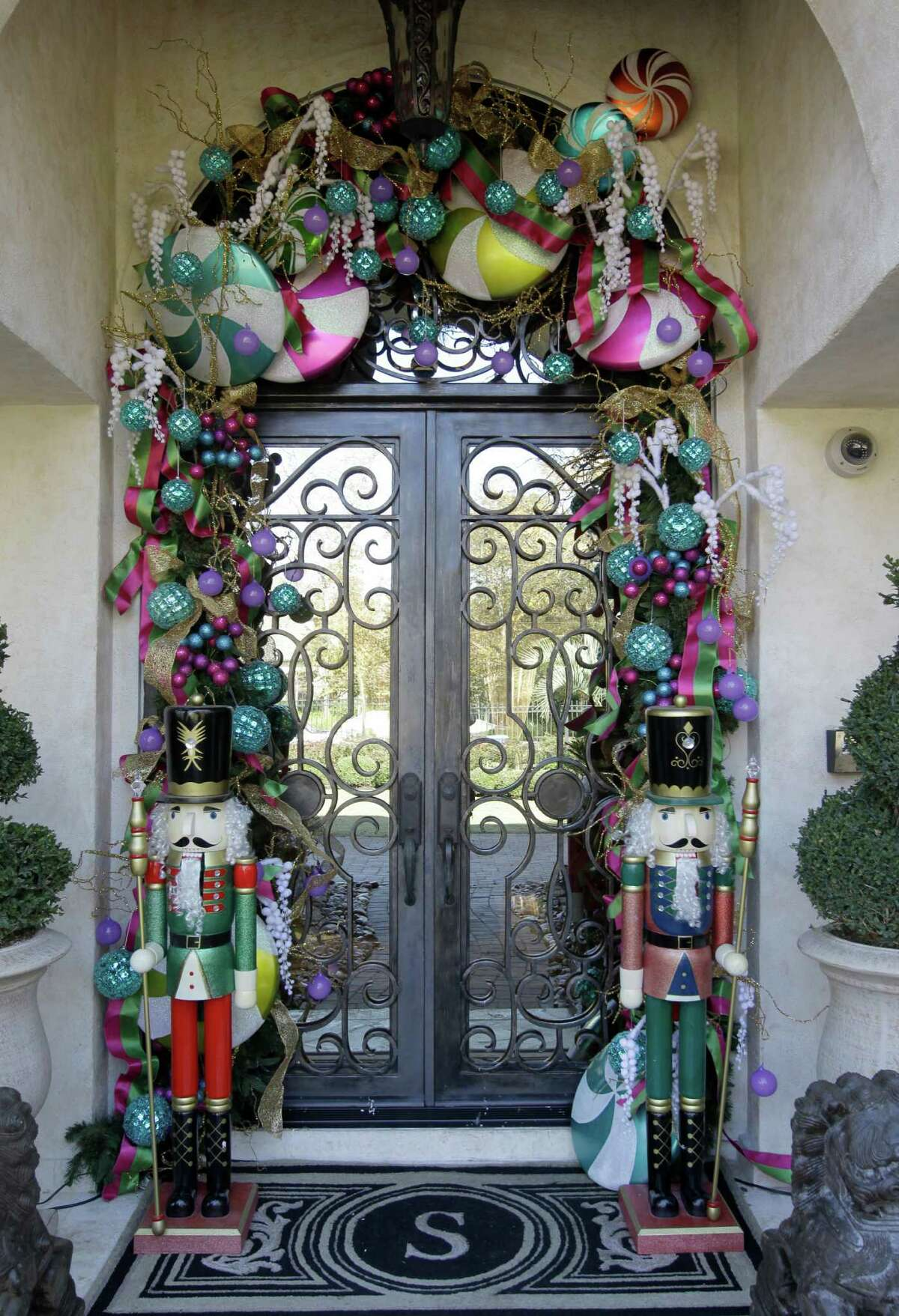 Nutcrackers stand guard at the front door, with big ornaments and oversize candies adding color overhead.