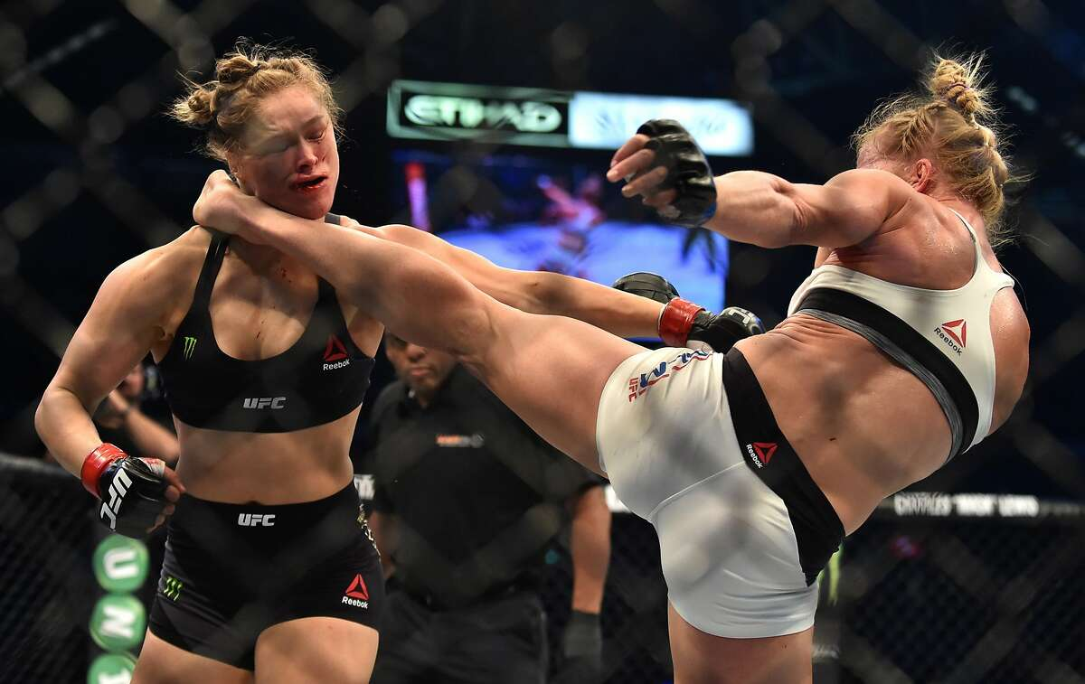 This file photo taken on November 15, 2015 shows Holly Holm of the US (R) landing a kick to the neck to knock out compatriot Ronda Rousey and win the UFC title fight in Melbourne on November 15, 2015.