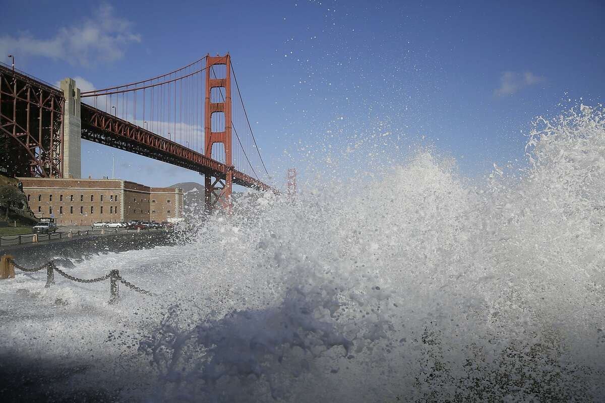High waves crash against the seawall at Fort Point with the Golden Gate Bridge in the background Friday, Dec. 11, 2015, in San Francisco. The biggest storm to hit the slopes of the Sierra Nevada this season triggered cheers Friday from the snow-starved ski resorts of Northern California and the businesses that surround them. Elsewhere in the drought-stricken state, rain and wind gusts prompted high surf warnings and repeated cautions from highway patrol to slow down when driving. (AP Photo/Eric Risberg)