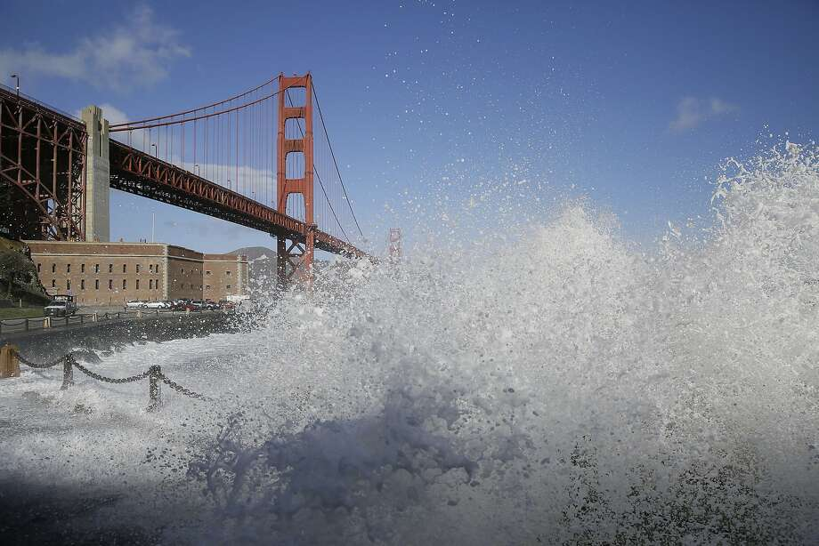 High waves crash against the seawall at Fort Point with the Golden Gate Bridge in the background during a recent big storm. Photo: Eric Risberg, Associated Press