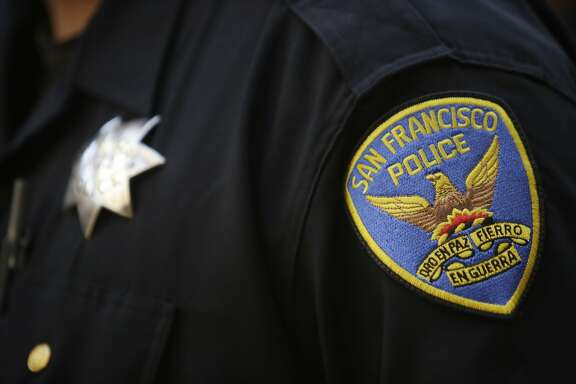 A San Francisco Police patch is seen on the uniform of an officer as he stands with members of the board of directors, members of the association and members of the community while Martin Halloran (not shown), San Francisco Police Officers Association president, speaks during a press conference at the San Francisco Police Officers Association headquarters on Wednesday, December 16, 2015 in San Francisco, Calif.