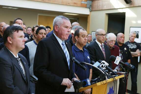 Martin Halloran (second from left), San Francisco Police Officers Association president, speaks during a press conference as members of the board of directors, members of the association and members of the community stand with him as he speaks at the San Francisco Police Officers Association headquarters on Wednesday, December 16, 2015 in San Francisco, Calif.