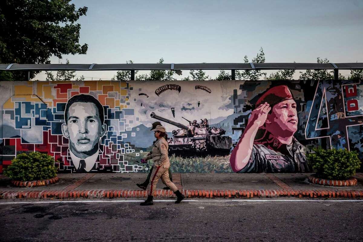 Two soldiers walks past a mural of Venezuela's late president Hugo Chavez, in Sabaneta, where Chavez was born, Dec. 11, 2015. Chavez's home state of Barinas joined the rest of the country in turning raw anger over economic hardship into a landslide victory for the political opposition in recent congressional elections. (Miguel Gutierrez/The New York Times)