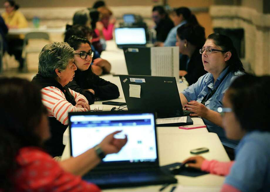 Assistors (right) help individuals sign up for 2016 health insurance plans through the federal marketplace during a December enrollment event. The total number of enrollees in Texas as of Jan. 2 was 1,108,935. Photo: Bob Owen /San Antonio Express-News / San Antonio Express-News