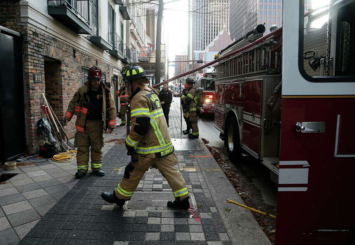 Houston Fire Department firefighters respond to a gasoline spill on Wednesday behind the Lancaster Hotel. District Chief Jeff Crow released a statement that firefighters would wash down and disperse the spill.