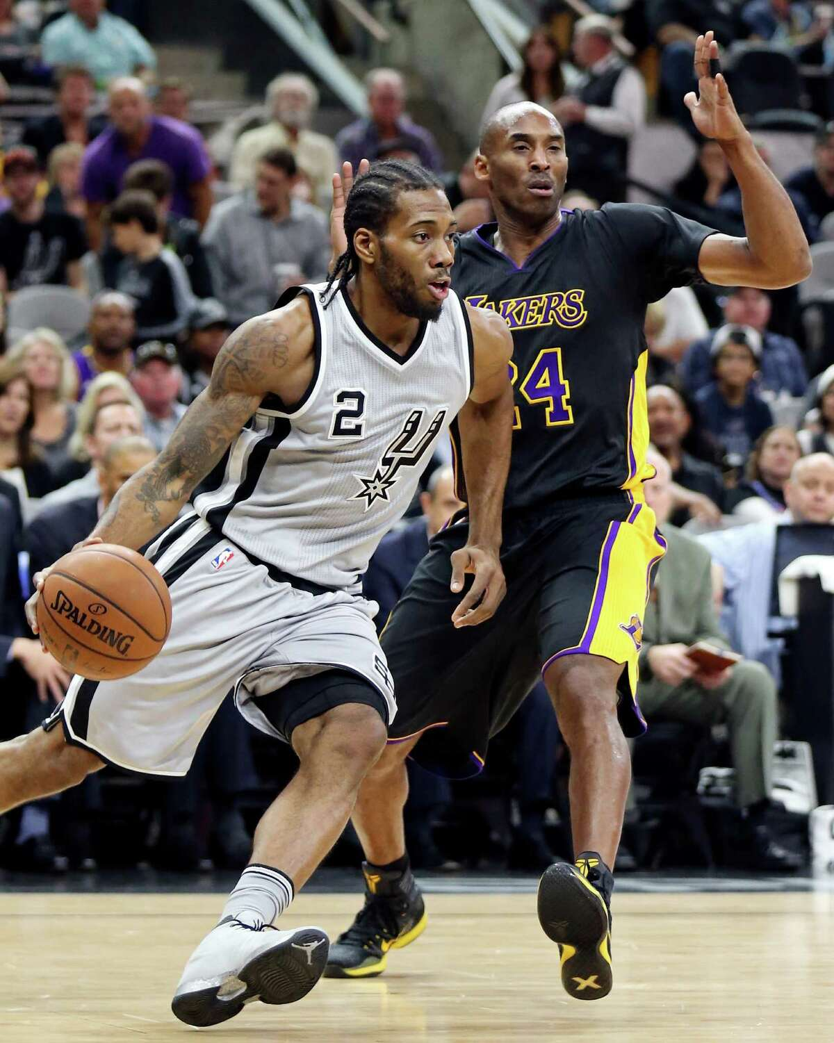 San Antonio Spurs' Kawhi Leonard drives around Los Angeles Lakers' Kobe Bryant during first half action Friday Dec. 11, 2015 at the AT&T Center.