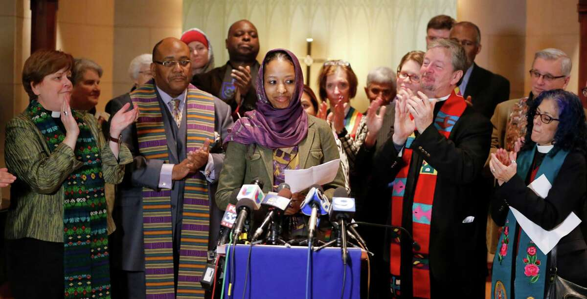 Wheaton College associate professor Larycia Hawkins Phd., center, is greeted with applause from supporters as she begins her remarks during a news conference Wednesday, Dec. 16, 2015, in Chicago. Hawkins, a Christian teaching political science at the private evangelical school west of Chicago, was put on leave Tuesday. In recent days, she began wearing a hijab, the headscarf worn by some Muslim women, to counter what she called the