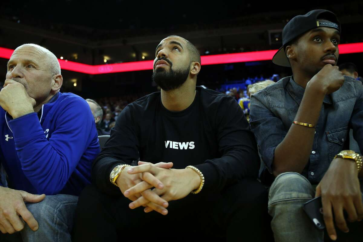 Drake watches the Golden State Warriors play Phoenix Suns in NBA game at Oracle Arena in Oakland, Calif., on Wednesday, December 16, 2015.
