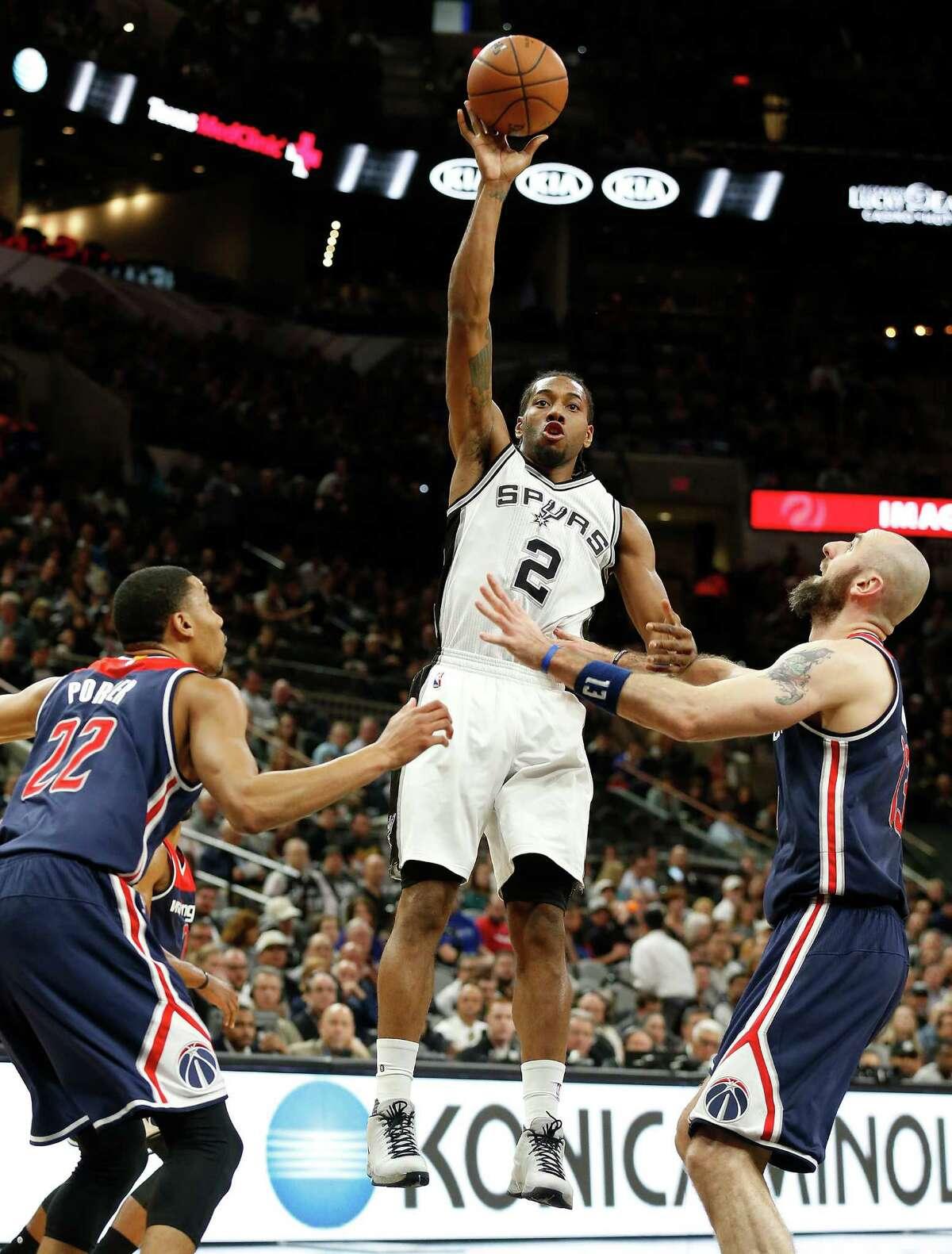 Spurs' Kawhi Leonard (02) takes a shot against Washington Wizards' Otto Porter Jr. (22) and Marcin Gortat (13) at the AT&T Center on Wednesday, Dec. 16, 2015. (Kin Man Hui/San Antonio Express-News)