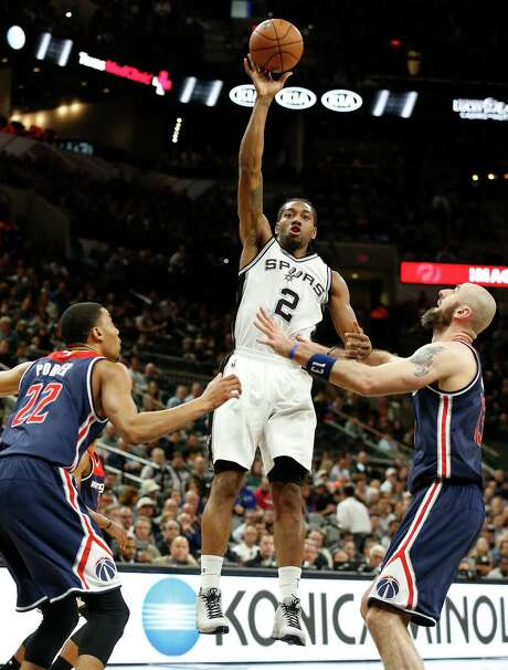 Spurs' Kawhi Leonard (02) takes a shot against Washington Wizards' Otto Porter Jr. (22) and Marcin Gortat (13) at the AT&T Center on Wednesday, Dec. 16, 2015. (Kin Man Hui/San Antonio Express-News) Photo: Kin Man Hui, Staff / San Antonio Express-News / ©2015 San Antonio Express-News