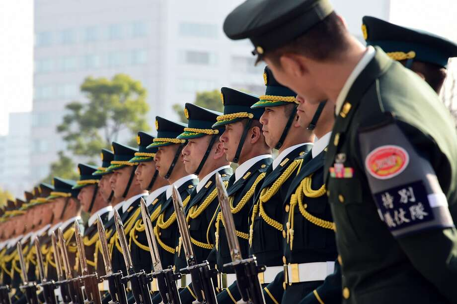 A senior official (R) of the Japanese Ground Self Defence Force checks the line of honour guards before a review by Japanese Prime Minister Shinzo Abe at the Defence Ministry in Tokyo on December 16, 2015. Abe delivered a speech before high-ranking officers of the defence ministry. Photo: Yoshikazu Tsuno, AFP / Getty Images