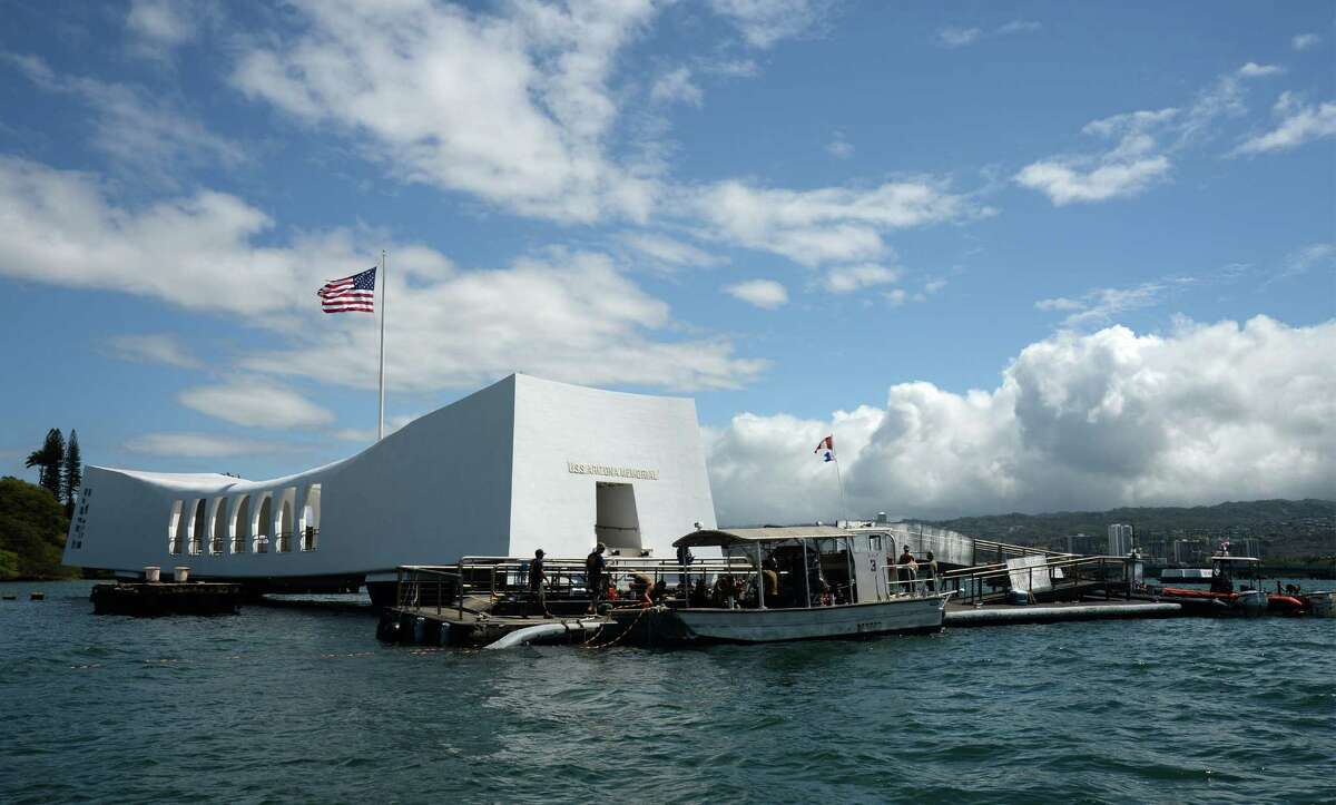 Now: A memorial of the U.S.S. Arizona stands in Pearl Harbor to honor some of the 1,177 sailors and Marines killed on the naval ship during the Japanese surprise attack on Pearl Harbor in 1941.
