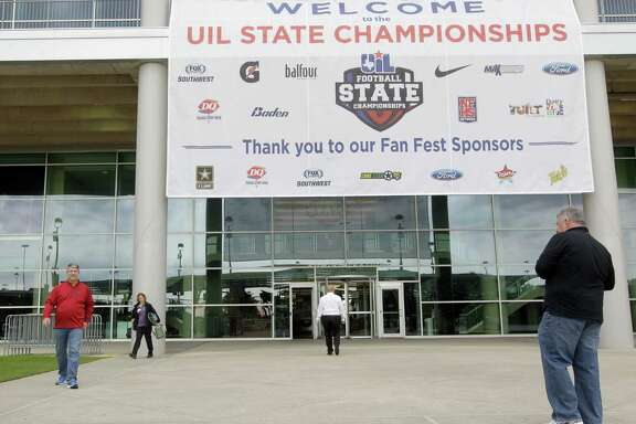 People walk outside of NGR Stadium near a State UIL banner at NRG Park, Wednesday, Dec. 16, 2015, in Houston. The UIL Football State Championship games will be played December 17-19 at NRG Stadium. ( Melissa Phillip  / Houston Chronicle )