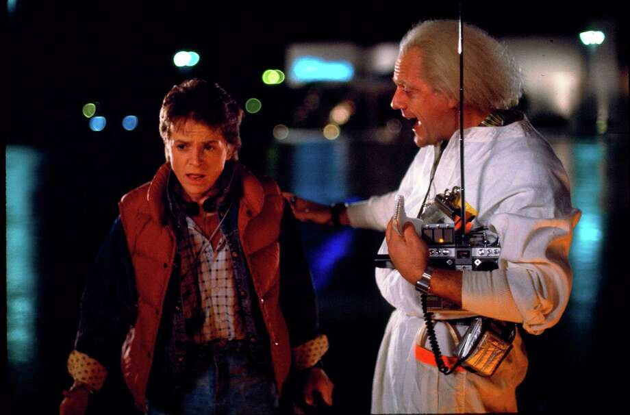 "This photo released by Universal Pictures shows, Michael J. Fox, left, as Marty McFly, and Christopher Lloyd as Dr. Emmett Brown, in a scene from the 1985 film, ""Back to the Future."" Co-stars Lea Thompson, Lloyd and others gather on Tuesday, June 30, 2015, for a special screening of the 1985 Michael J. Fox time-travel blockbuster, to be presented on the massive Hollywood Bowl screen with musical score performed live and orchestra conducted by the original composer, Alan Silvestri. (Universal Pictures via AP) Photo: Associated Press / Universal Pictures"