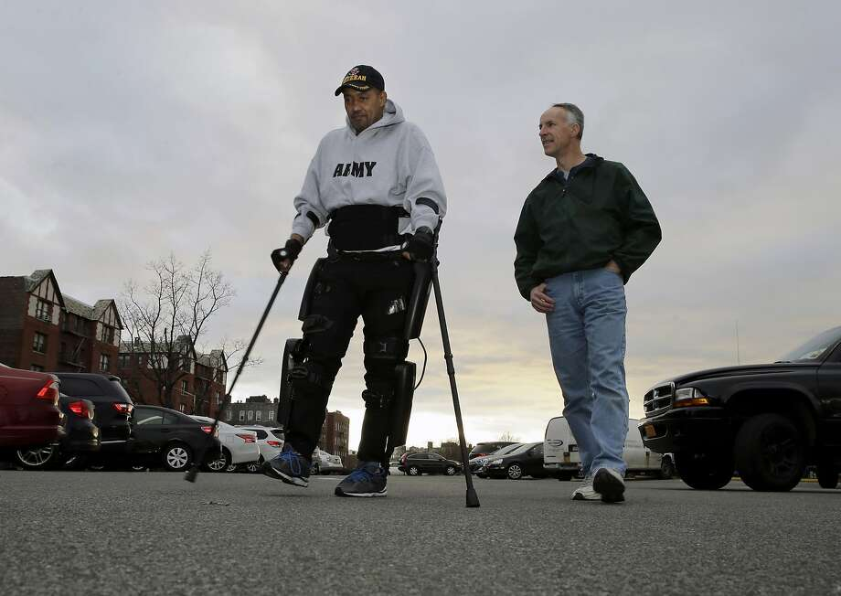 Robotics service engineer Tom Coulter watches paralyzed Army veteran Gene Laureano walk with the aid of a robotic device. Photo: Mel Evans, Associated Press