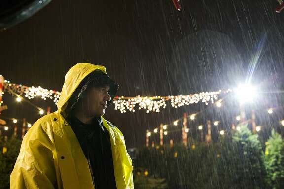 Ramiro Mejia stands in a light rain while waiting for customers at the Delancey Street Foundation Christmas tree lot at Pier 32 in San Francisco on Thursday, December 10, 2015. The foundation is a residential rehabilitation organization for ex-convicts and substance abusers. They have a restaurant, catering service, moving company and during the holidays, they have Christmas tree lots, which are run and managed by the Delancey Street residents. The proceeds go to funding their operations for the year.
