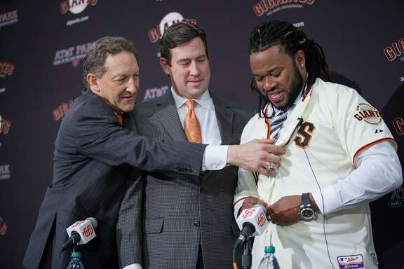 San Francisco Giants CEO Larry Baer and general manager Bobby Evans present Johnny Cueto with his Giants jersey during a news conference at AT&T Park, Thursday, Dec. 17, 2015, in San Francisco, Calif. The Giants introduced Cueto as their new official player today. Cueto, a 29-year-old pitcher, signed a six-year, $130 million contract with the Giants.