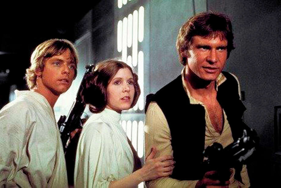 """This photo provided by Twentieth Century Fox Home Entertainment shows, Mark Hamill, from left, as Luke Skywalker, Carrie Fisher as Princess Leia Organa, and Harrison Ford as Hans Solo in the original 1977 """"Star Wars: Episode IV - A New Hope"""" film, included in the new Blu-ray release of  """"Star Wars: The Complete Saga"""" out on Oct. 13, 2015. The new film, """"Star Wars: The Force Awakens,"""" opens in U.S. theaters on Dec. 18, 2015. (Twentieth Century Fox Home Entertainment via AP) ORG XMIT: CAET453 / Twentieth Century Fox Home Entertainment"""