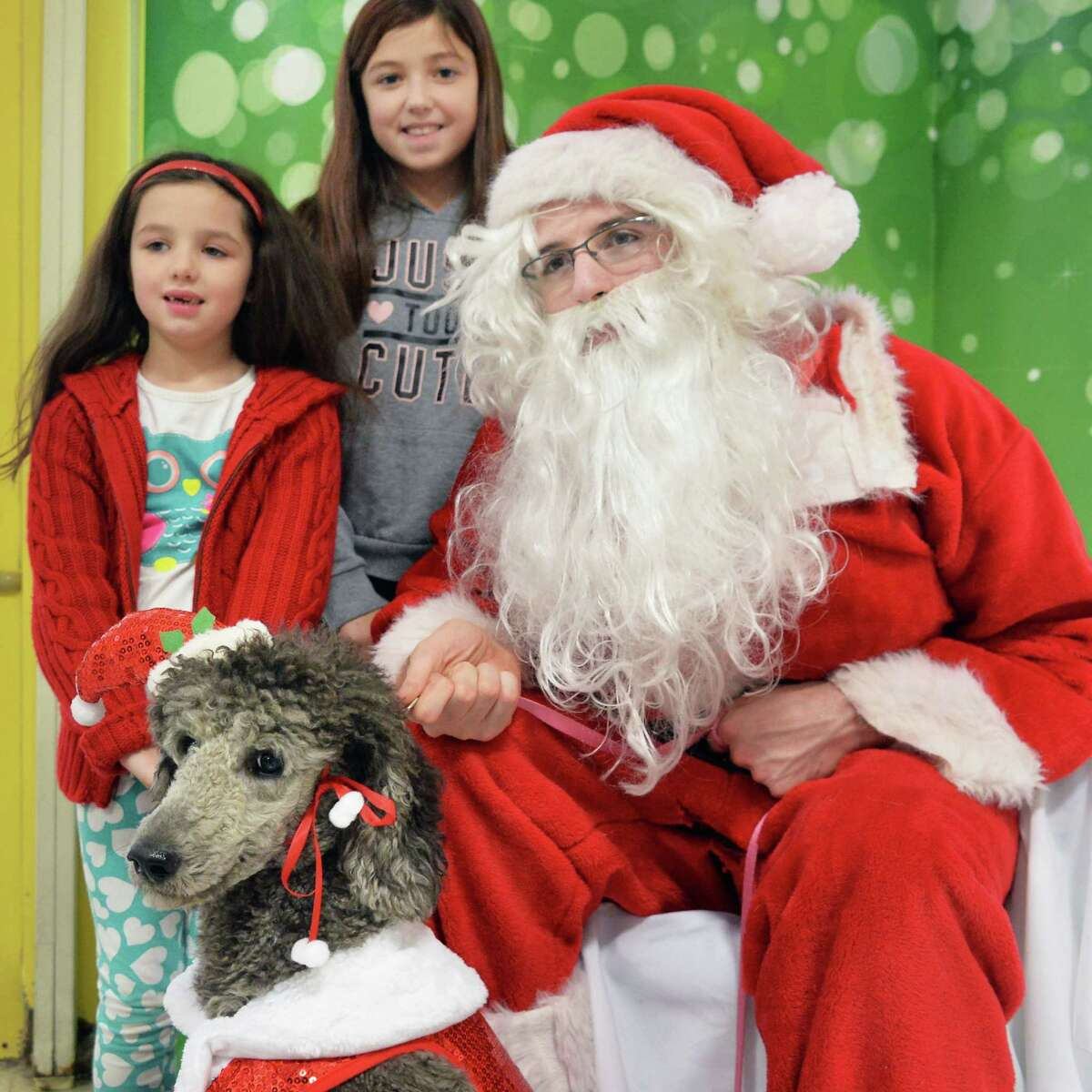 Talia, 6, left, and her sister Sage Rysedorph, 11, of Colonie pose with their Grandmother's poodleTori for a photo with Santa at Petco Saturday Dec. 12, 2015 in Colonie, NY. (John Carl D'Annibale / Times Union)
