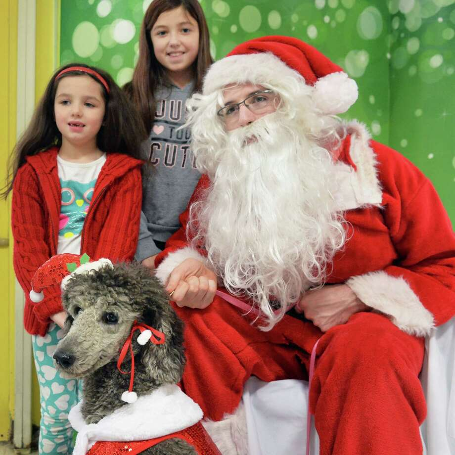 Talia, 6, left, and her sister Sage Rysedorph, 11, of Colonie pose with their Grandmother's poodleTori for a photo with Santa at Petco Saturday Dec. 12, 2015 in Colonie, NY.  (John Carl D'Annibale / Times Union) Photo: John Carl D'Annibale / 10034637A