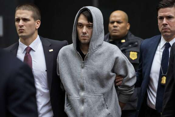 Martin Shkreli, the former hedge fund manager under fire for buying a pharmaceutical company and ratcheting up the price of a life-saving drug, is escorted by law enforcement agents in New York Thursday, Dec. 17, 2015, after being taken into custody following a securities probe. A seven-count indictment unsealed in Brooklyn federal court Thursday charged Shkreli with conspiracy to commit securities fraud, conspiracy to commit wire fraud and securities fraud. (AP Photo/Craig Ruttle)