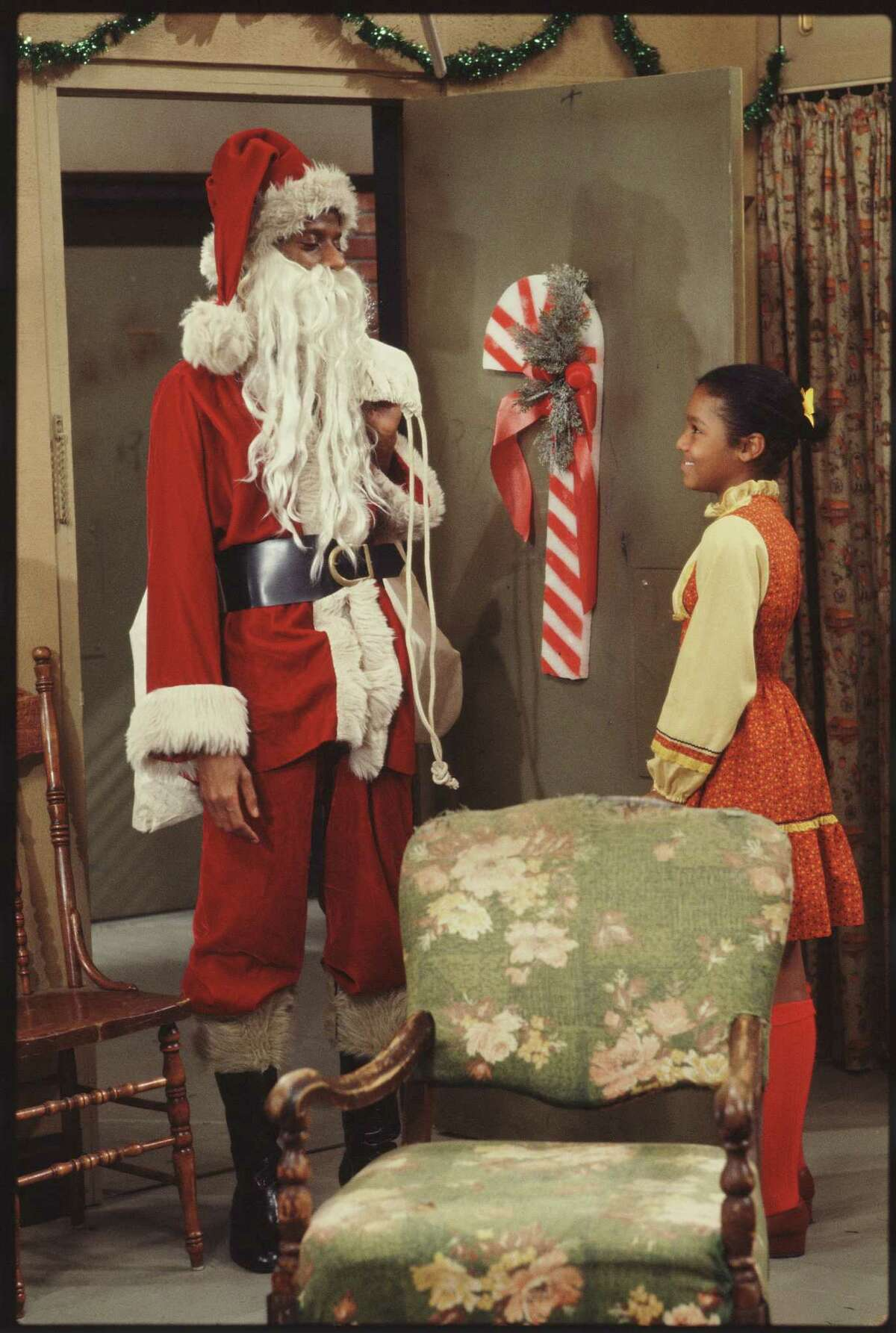 American child actress Janet Jackson (right) opens the door for actor Jimmie Walker, dressed as Santa Claus, in a scene from the television show 'Good Times,' Los Angeles, California, 1977.