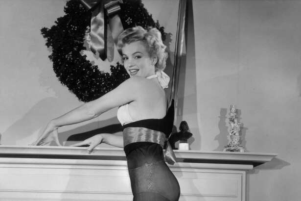 American actor Marilyn Monroe (1926 - 1962) poses while standing inside an oversized nylon Christmas stocking beside a fireplace, 1951. Monroe wears a two-piece bathing suit.