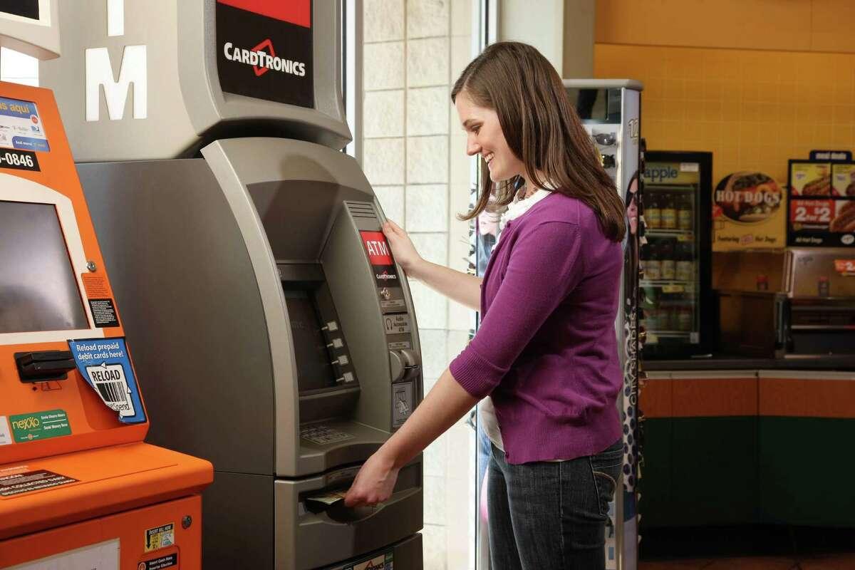 Woman uses a Cardtronics ATM.