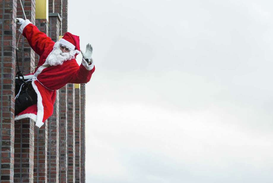 "A man dressed as Father Christmas, aka Santa Claus, descends the Kollhoff tower in Berlin as part of a yearly stunt before the festive season. A reader says Christmas is Christmas and should not be described in politically correct terms such as ""the holiday season."" Photo: JOHN MACDOUGALL /AFP / Getty Images / AFP"