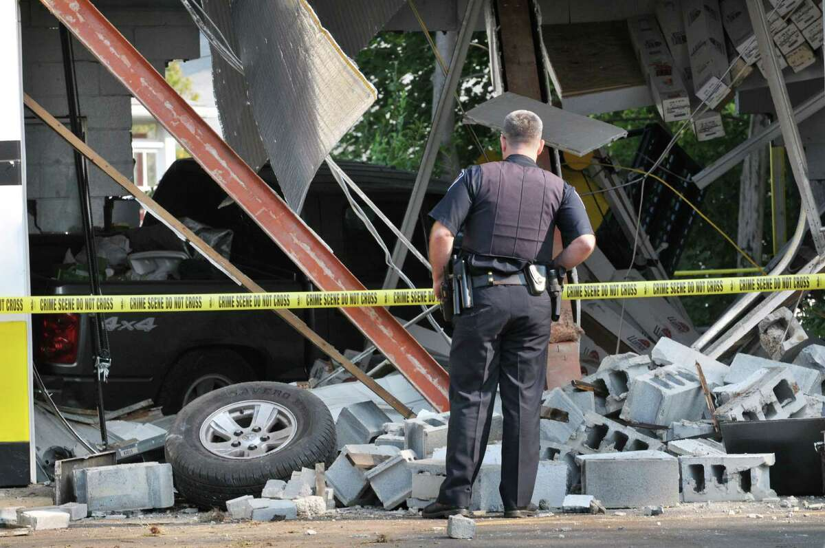 A Colonie Police officer surveys damage to the Tint King garage on Central Avenue Wednesday morning, Sept. 2, 2015, after a pickup truck left the road late Tuesday, took out a utility pole and slammed into the building in Colonie, N.Y. (Will Waldron/Times Union)