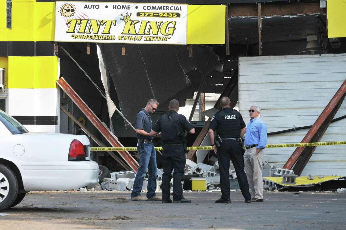 Colonie Police and town officials inspect damage to the Tint King garage on Central Avenue Wednesday morning, Sept. 2, 2015, after a pickup truck left the road late Tuesday, took out a utility pole and slammed into the building in Colonie, N.Y. (Will Waldron/Times Union)