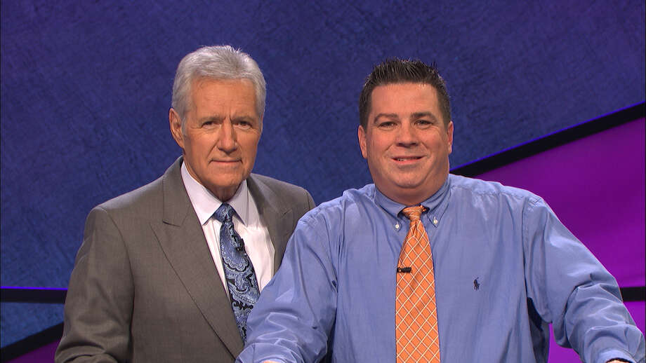 """Jay O'Brien, a physics instructor from Waterford, is shown with """"Jeopardy!"""" host Alex Trebeck. (Photo courtesy of Jeopardy Productions, Inc.)"""