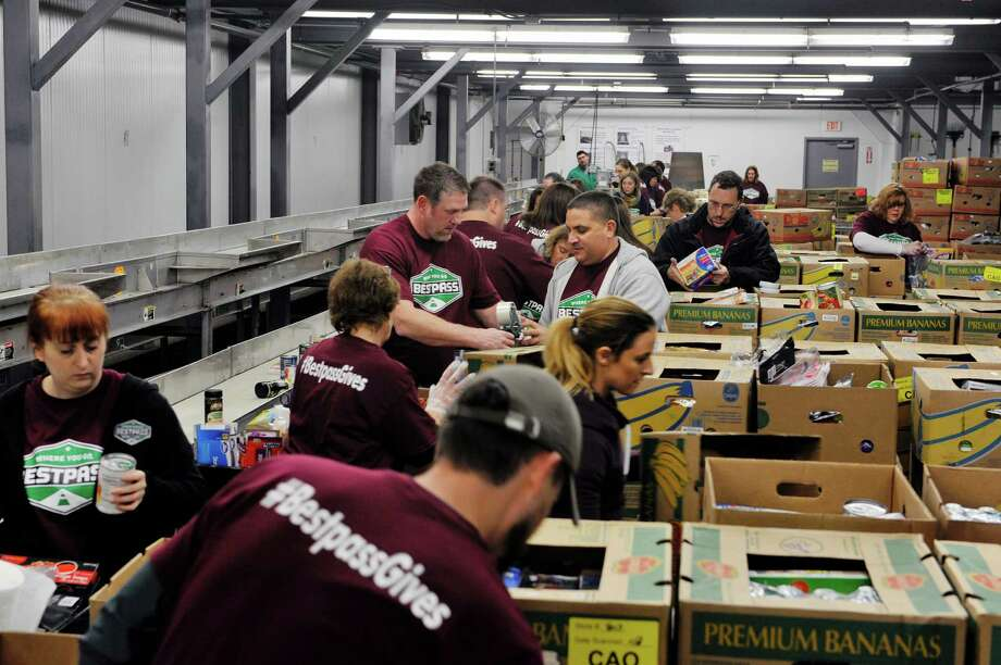 Employees of Bestpass volunteer their time sorting and boxing donated food items at the Regional Food Bank of Northeastern New York on Thursday, Dec. 17, 2015, in Latham, N.Y.  This is the first year that the company has volunteered at the food bank but company representatives said they plan on making it a yearly event.  All 35 of Bestpass local employees helped out on Thursday.  The company which is headquartered in Albany, streamlines tolling management  for the trucking industry nationwide.  (Paul Buckowski / Times Union) Photo: PAUL BUCKOWSKI / 10034683A