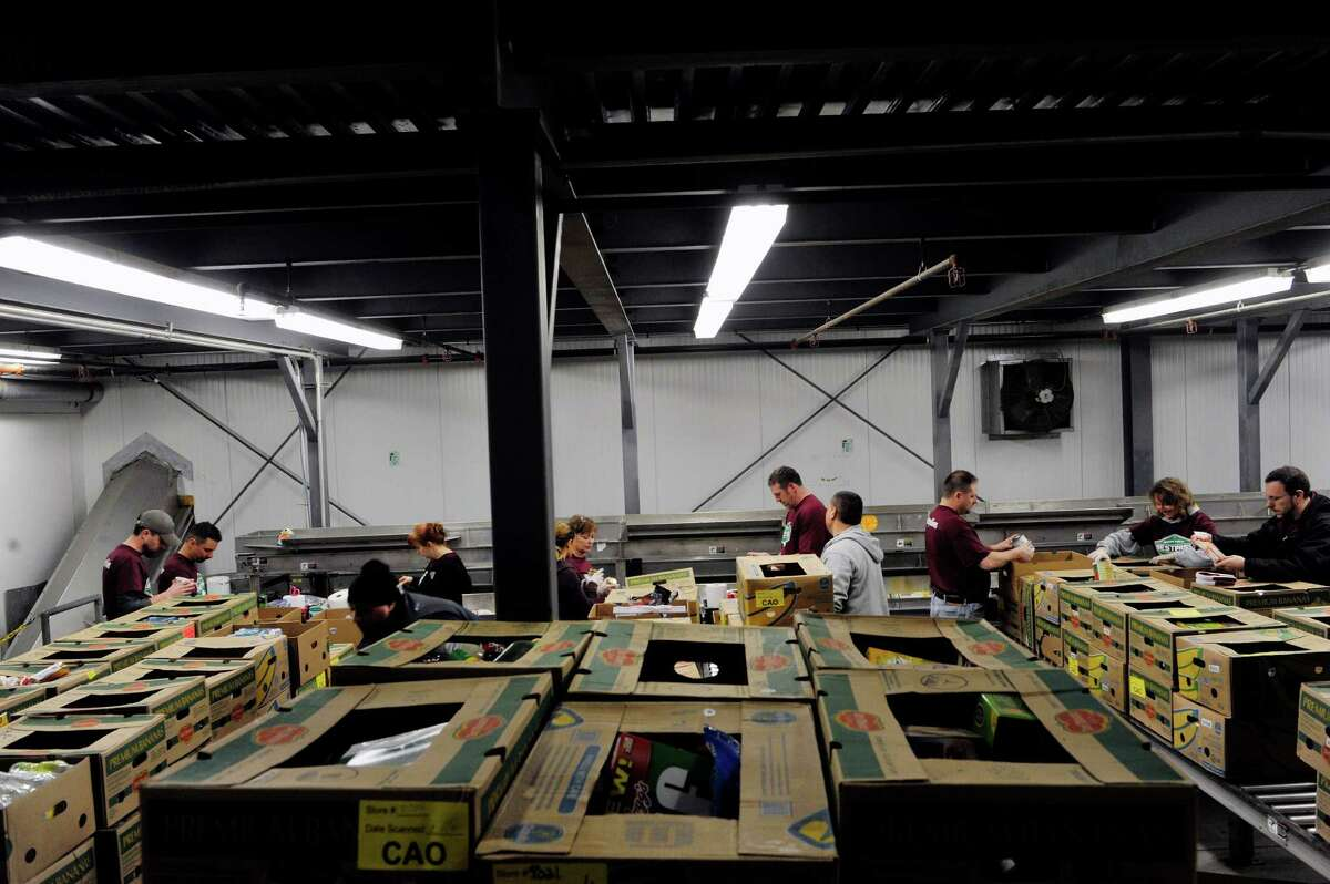 Employees of Bestpass volunteer their time sorting and boxing donated food items at the Regional Food Bank of Northeastern New York on Thursday, Dec. 17, 2015, in Latham, N.Y. This is the first year that the company has volunteered at the food bank but company representatives said they plan on making it a yearly event. All 35 of Bestpass local employees helped out on Thursday. The company which is headquartered in Albany, streamlines tolling management for the trucking industry nationwide. (Paul Buckowski / Times Union)